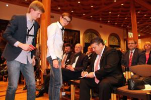 Jugendliche erobern sich ein Autogramm von Sigmar Gabriel