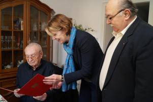 Ulrike Bahr überreicht die Ehrenurkunde und die goldene Anstecknadel.
